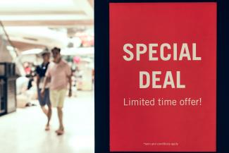 adults walking by a sign advertising a special deal