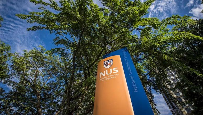 NUS Business School sign with school logo juxtaposed against trees and sky