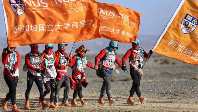 NUS business school students in the Gobi desert holding flags with the NUS logo